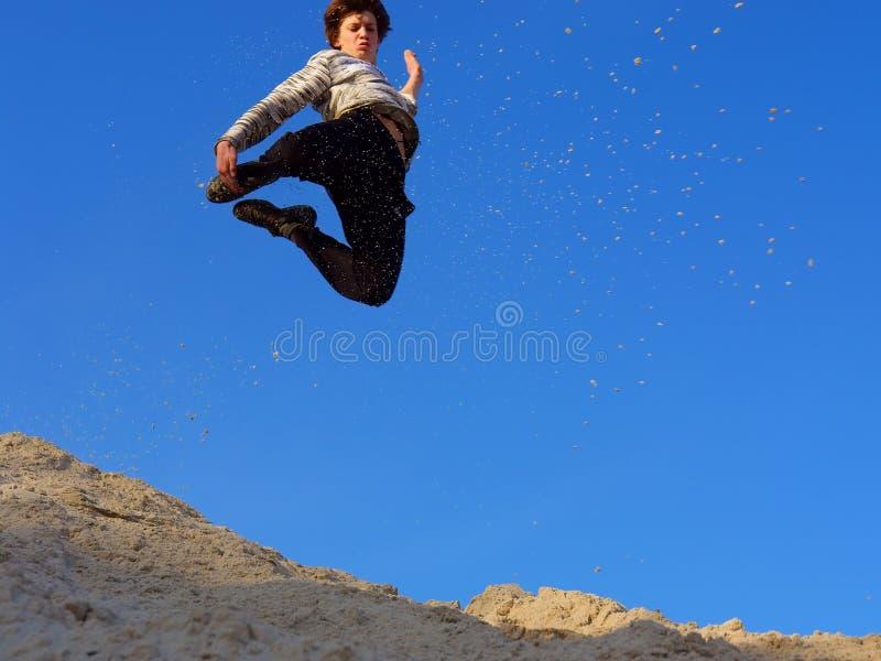 Jugendlicher springt vom Sandhügel stockfoto
