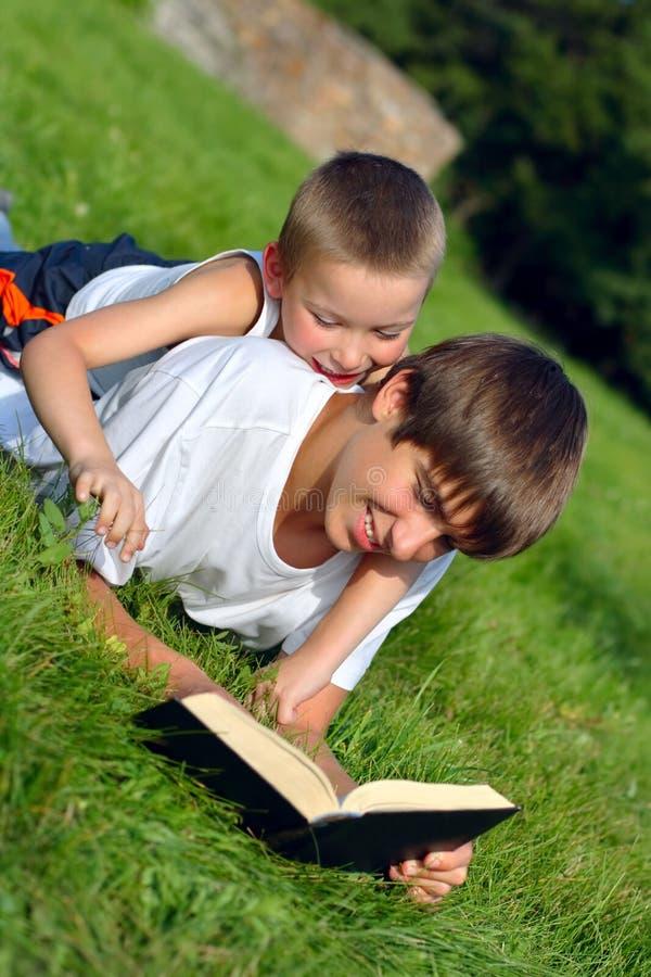 Jugendlicher und Kind mit einem Buch lizenzfreies stockfoto