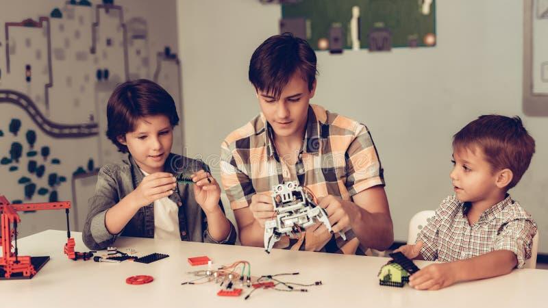 Jugendlicher und zwei Jungen, die zu Hause Roboter konstruieren stockfotos