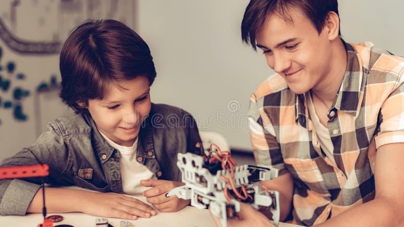 Jugendlicher und zwei Jungen, die zu Hause Roboter konstruieren lizenzfreie stockbilder
