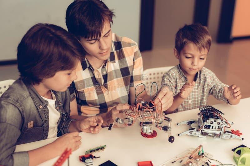 Jugendlicher und zwei Jungen, die zu Hause Roboter konstruieren stockfoto