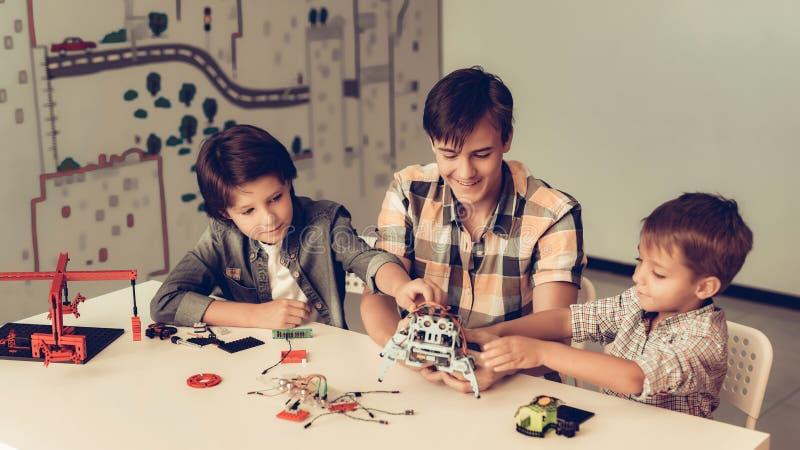 Jugendlicher und zwei Jungen, die zu Hause Roboter konstruieren lizenzfreies stockbild