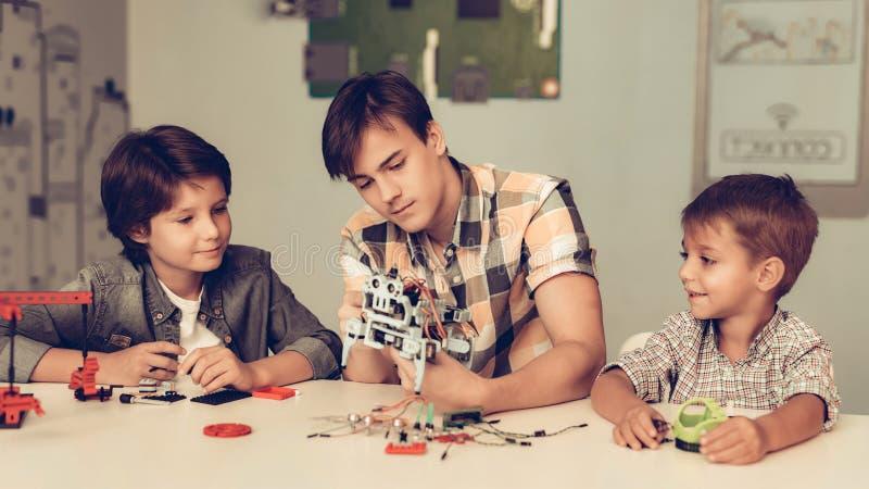 Jugendlicher und zwei Jungen, die zu Hause Roboter konstruieren lizenzfreies stockfoto
