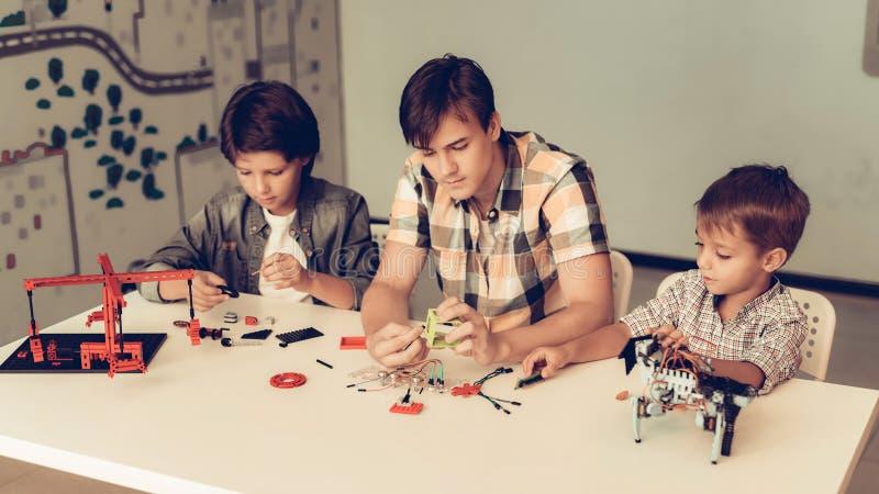 Jugendlicher und zwei Jungen, die zu Hause Roboter konstruieren lizenzfreie stockfotos