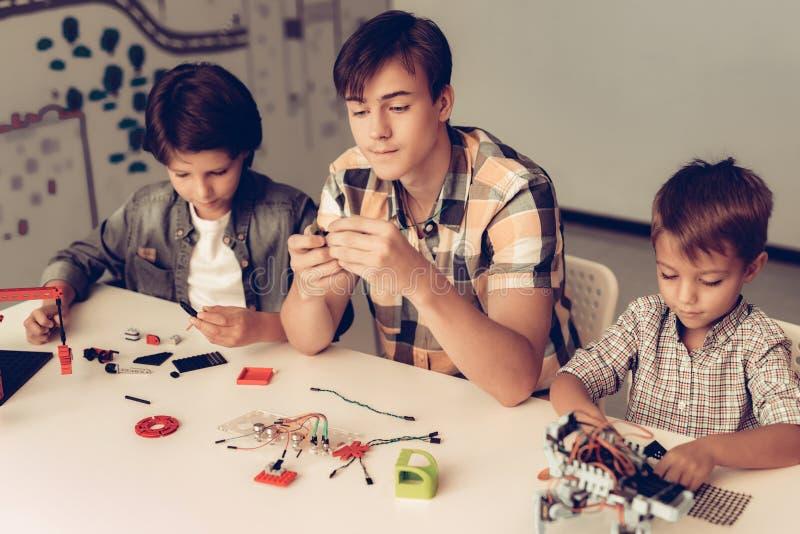 Jugendlicher und zwei Jungen, die zu Hause Roboter konstruieren stockbild
