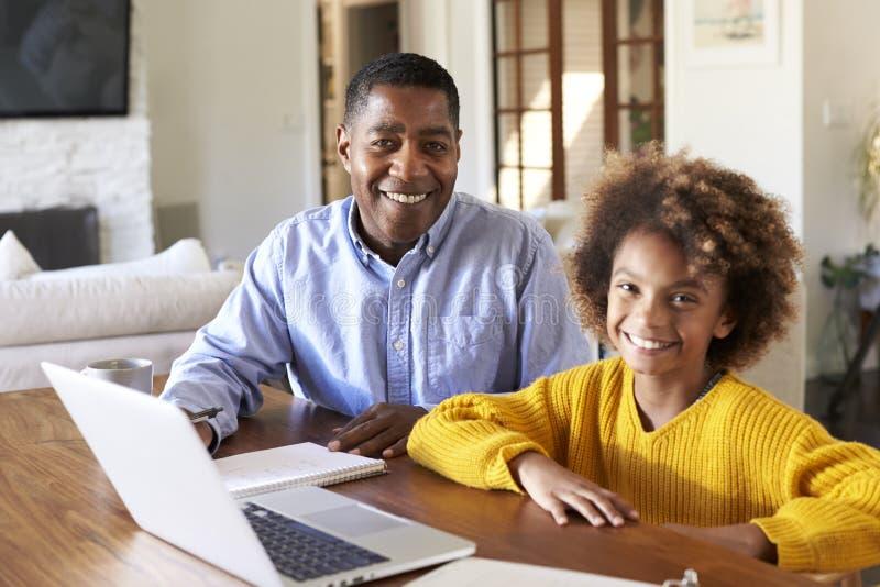 Jugendliches Afroamerikanermädchen und ihr männlicher Haupttutor, die an einem Tisch im Esszimmer oben lächelt zur Kamera, Abschl stockfotografie