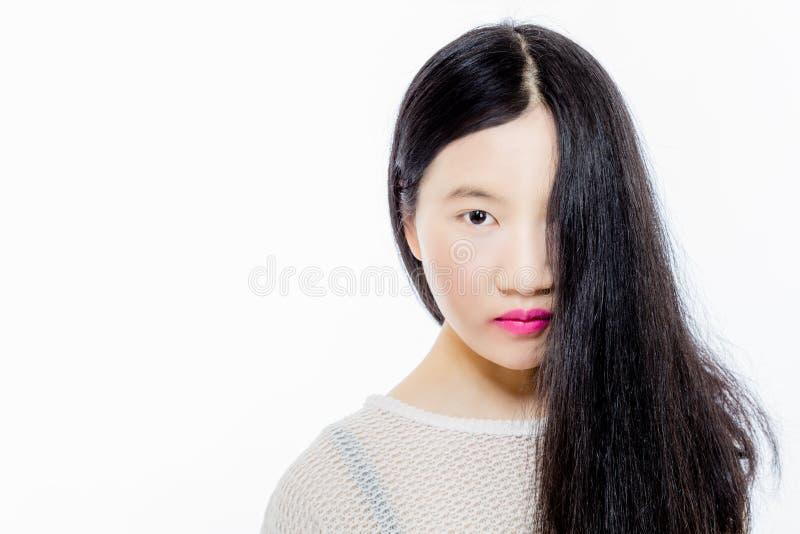 Jugendliches asiatisches Mädchen mit halbem Gesicht der Haarbedeckung stockbild