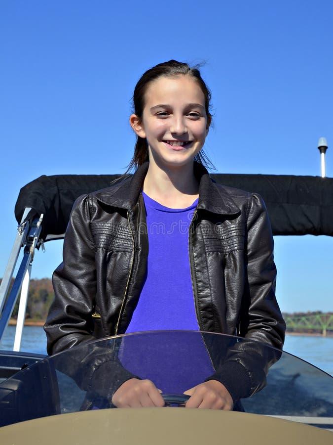 Jugendliches Mädchen, das erlernt, ein Boot anzutreiben lizenzfreie stockbilder