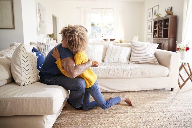 Jugendliches Mädchen, das ihren Vater im Wohnzimmer umarmt, nachdem ihm ein handgemachtes Geschenk, Seitenansicht gegeben worden  lizenzfreies stockfoto