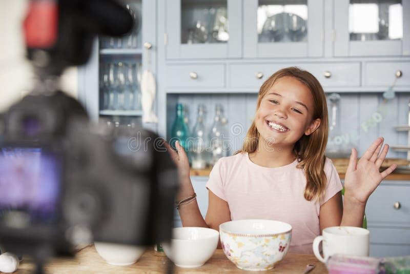 Jugendliches Mädchenvideo, das in der Küche wellenartig bewegt ihre Hände blogging ist stockfoto