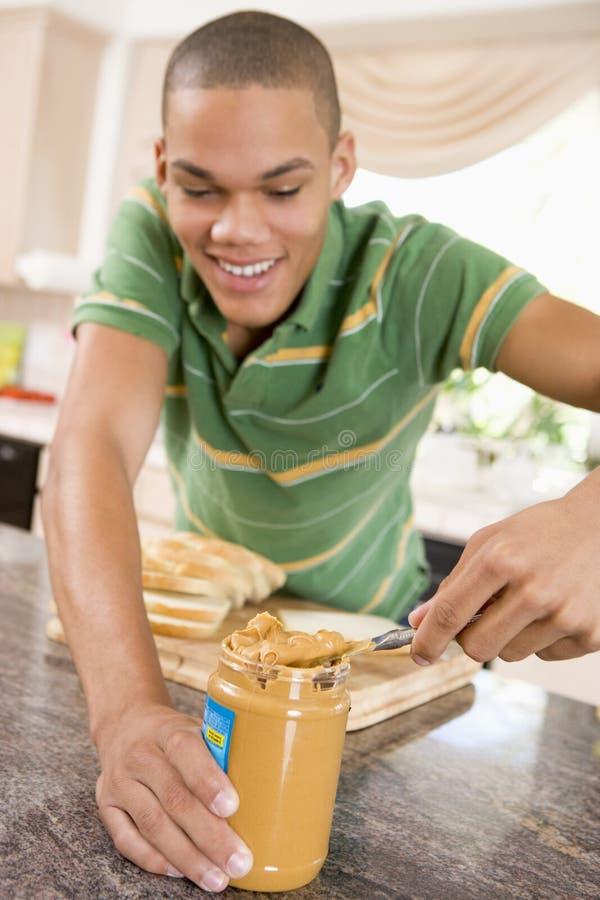Jugendliches männliches bildenerdnußbutter-Sandwich stockbilder