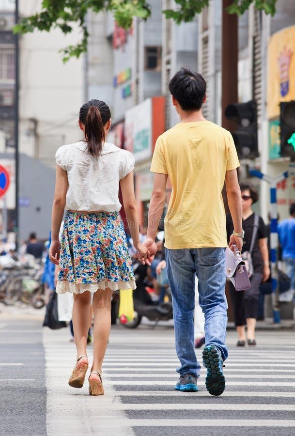 Jugendliches Paar geht Hand in Hand auf Zebrastreifen, Nanjing, China stockbild