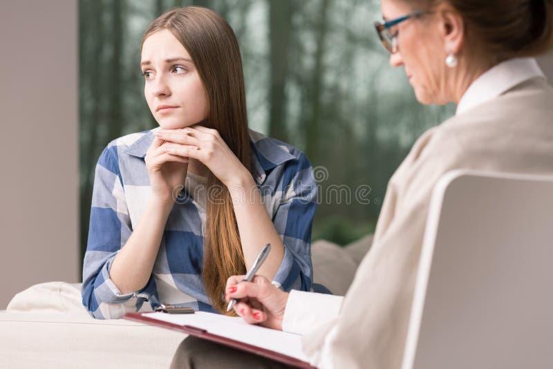 Jugendliches unsicheres Mädchen, das mit Psychotherapeuten spricht lizenzfreies stockbild
