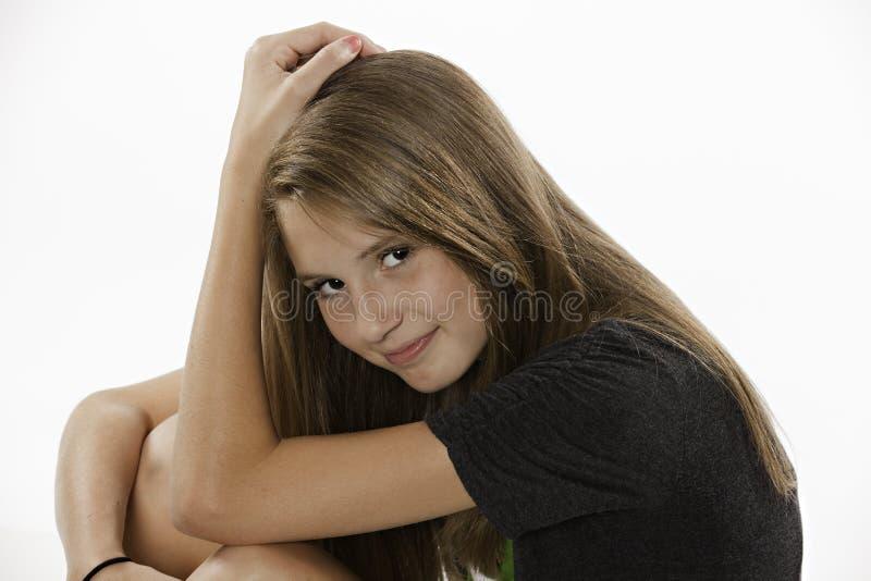 Jugendliches weibliches Mädchen, das auf Weiß sitzt lizenzfreies stockfoto