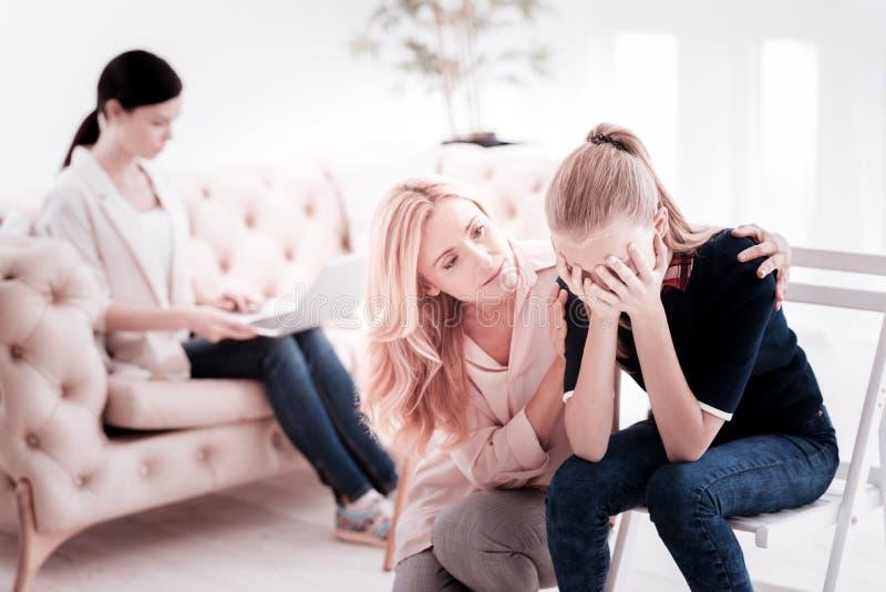 Jugendlicheschreien und ihre nette aufmerksame Mutter sie umarmend lizenzfreie stockbilder