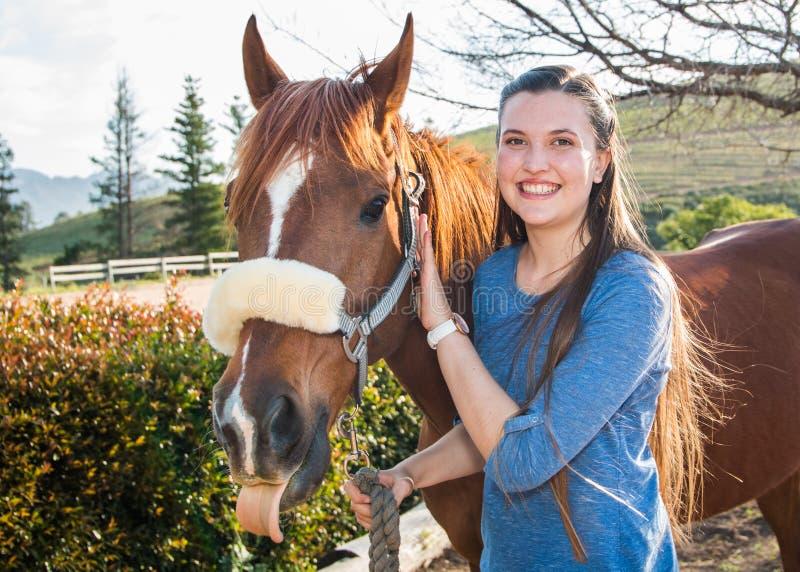 Jugendlichestellung mit ihrem Kastanie Araberpferd, welches das Kameralächeln betrachtet stockfoto