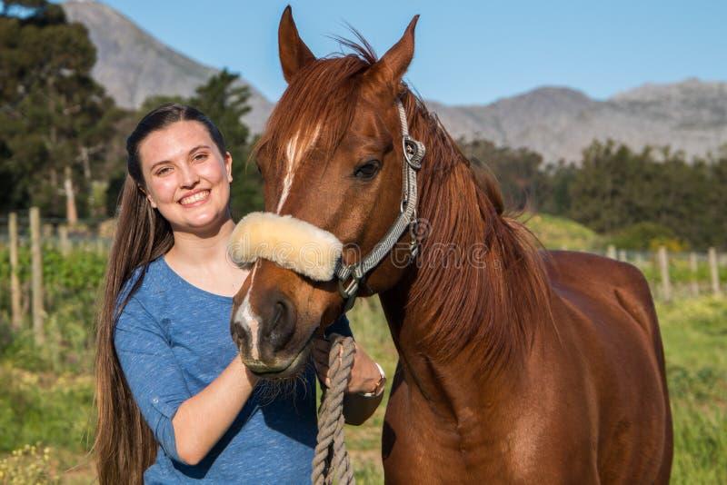 Jugendlichestellung mit ihrem Kastanie Araberpferd, welches die Kamera betrachtet lizenzfreie stockfotos