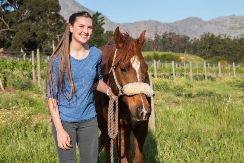 Jugendlichestellung mit ihrem Kastanie Araberpferd, welches die Kamera betrachtet lizenzfreies stockbild