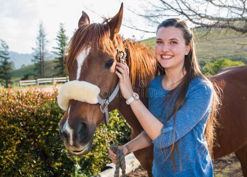 Jugendlichestellung mit ihrem Kastanie Araberpferd, welches die Kamera betrachtet stockbilder
