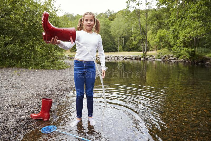 Jugendlichestellung in tragenden Socken eines Flusses gießt Wasser aus ihrem roten Gummistiefel heraus lizenzfreie stockfotografie