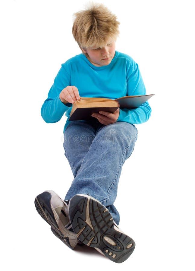 Jugendlichjunge, der ein Buch liest stockfoto