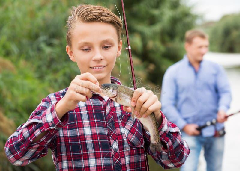 Jugendlichjunge, der Fische auf Haken betrachtet lizenzfreies stockfoto