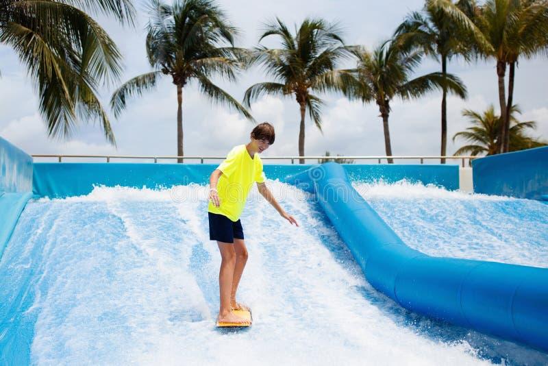 Jugendlichjunge, der in Strandwellensimulator surft stockfotos