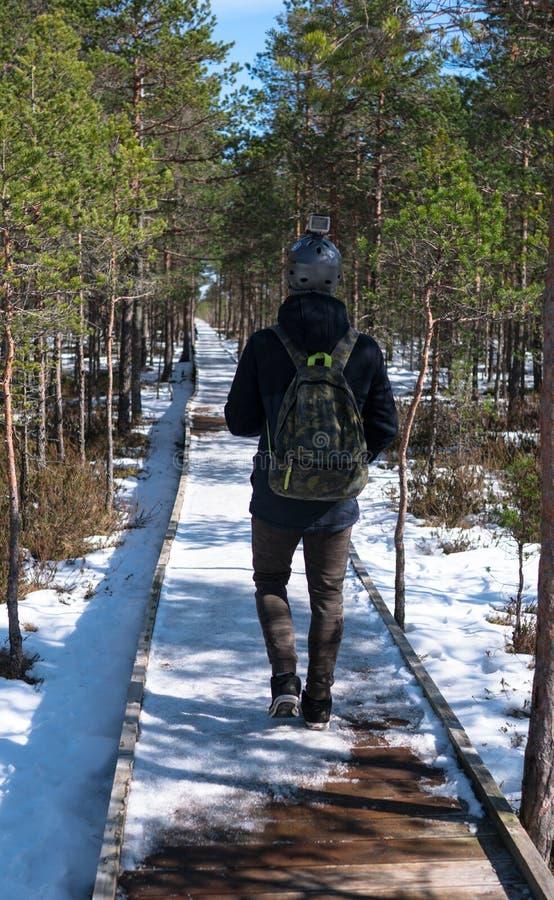 Jugendlichjunge, der in Wald mit Aktionskamera auf seinem Sturzhelm geht Militärrucksack und Hosen Hölzerne Straße in schneebedec lizenzfreies stockbild