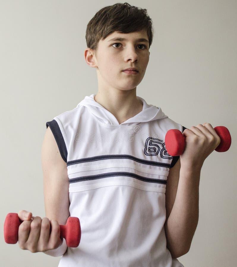 Jugendlichjunge in einem weißen Hemd ohne Ärmel tut Übungen mit Dummköpfen stockbild