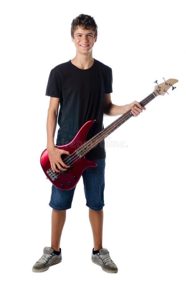 Jugendlichjunge mit dem Bass-Gitarrenlächeln lizenzfreie stockbilder