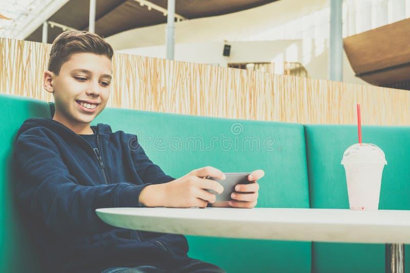 Jugendlichjunge sitzt bei Tisch im Café, trinkt Milchshaken und benutzt Smartphone Junge spielt Spiele auf dem Smartphone und gra lizenzfreie stockfotos