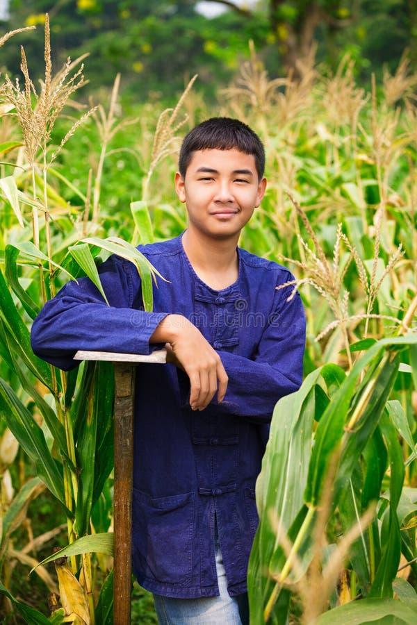 Jugendlichjunge in Thailands Landwirt dresss am Maisfeld stockfotografie