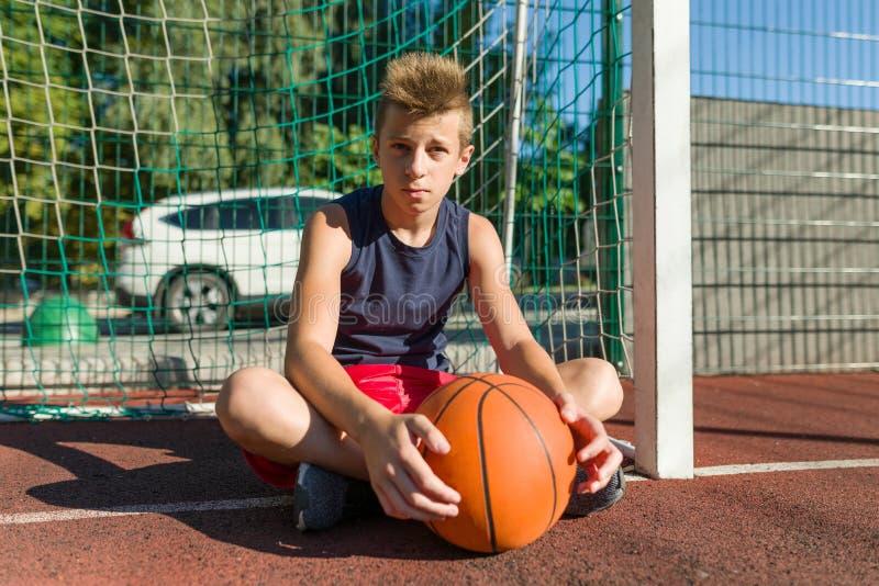 Jugendlichjungen-Straßenbasketball-spieler auf dem Stadtbasketballplatz lizenzfreie stockbilder