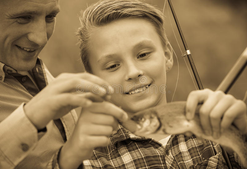Jugendlichjungenholding-Fangfische auf Haken lizenzfreies stockfoto