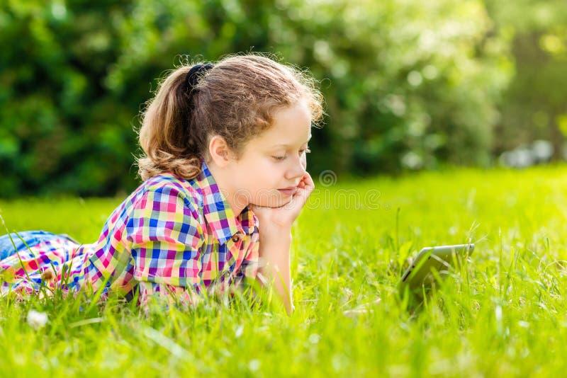 Jugendlichmädchen, das auf dem Gras mit digitaler Tablette oder eBook, Porträt im Freien liegt stockbild