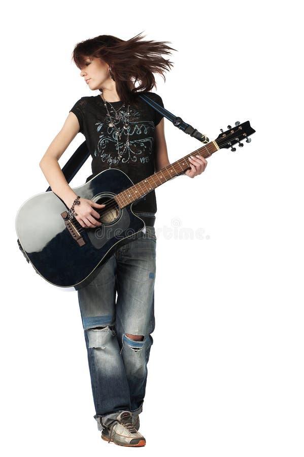 Jugendlichmädchen, das eine Akustikgitarre spielt stockfotografie