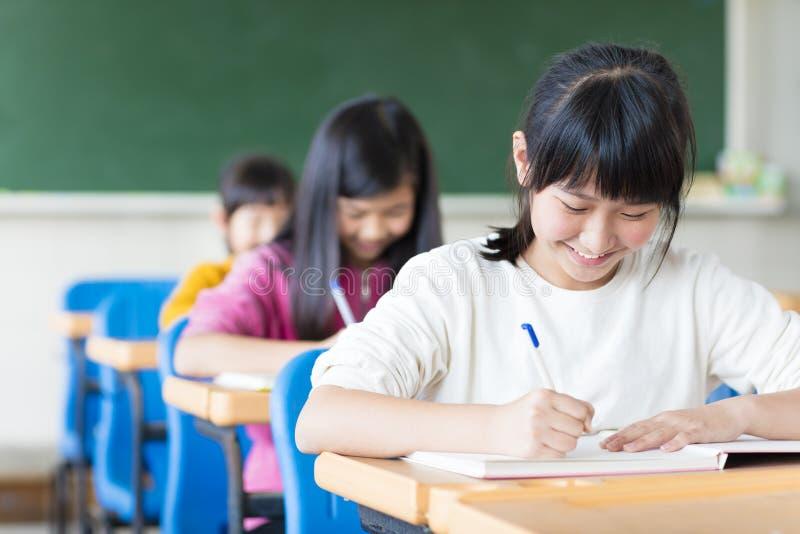 Jugendlichmädchen, das im Klassenzimmer lernt stockfotos