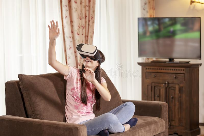 Jugendlichmädchen, das Spaß mit Gläsern der virtuellen Realität zu Hause hat stockfoto
