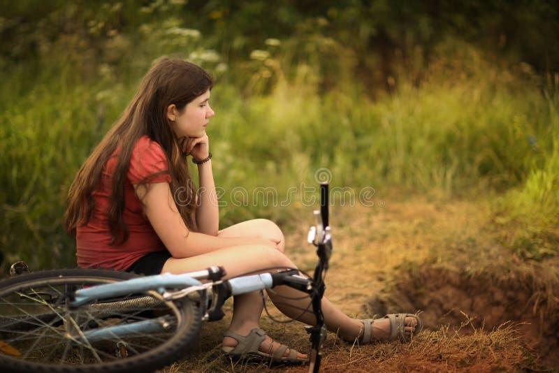 Jugendlichmädchen-Fahrfahrrad auf Landstraße durch den Wald lizenzfreies stockbild