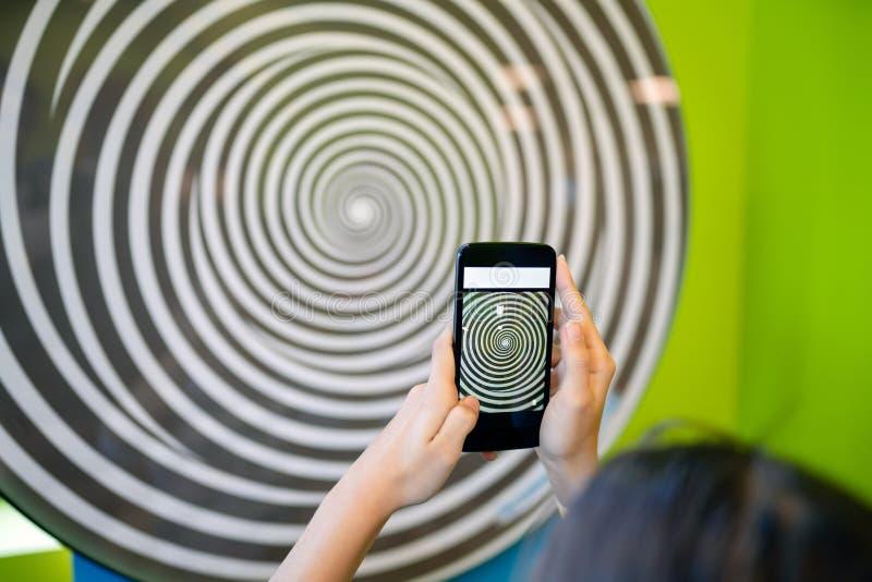 Jugendlichmädchen hypnotisiert durch wirbelnde Spirale stockfotografie