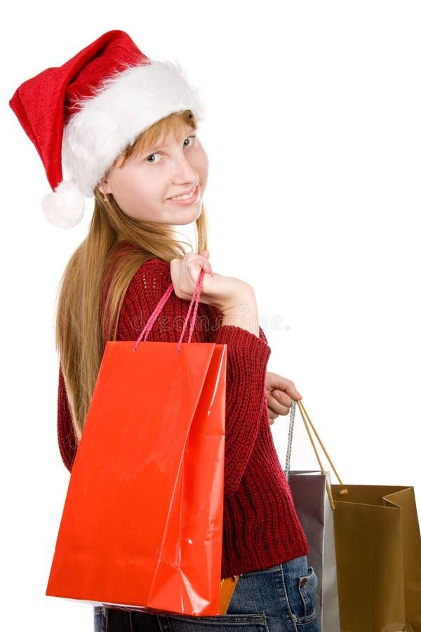 Jugendlichmädchen im Weihnachtshut mit Einkaufenbeuteln lizenzfreies stockbild
