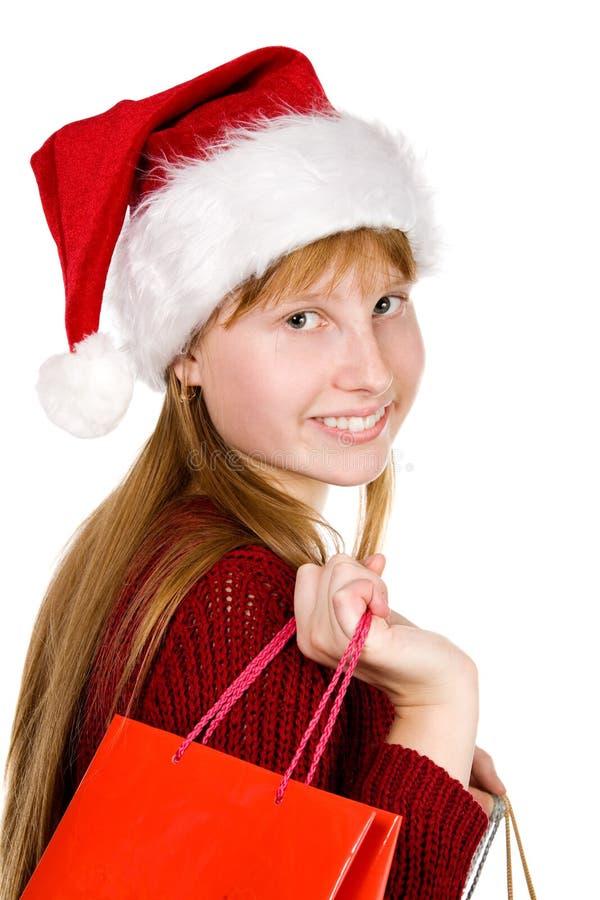 Jugendlichmädchen im Weihnachtshut mit Einkaufenbeuteln stockbild