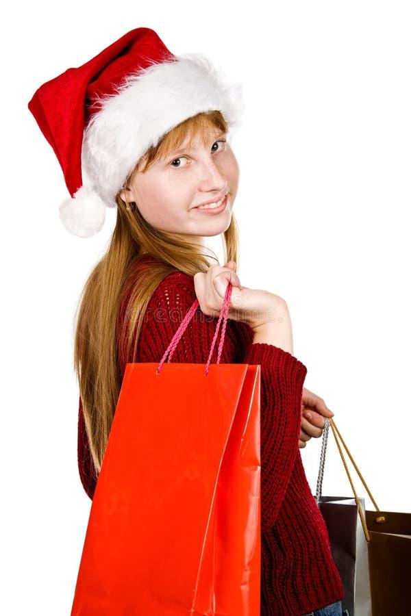 Jugendlichmädchen im Weihnachtshut mit Einkaufenbeuteln lizenzfreies stockfoto