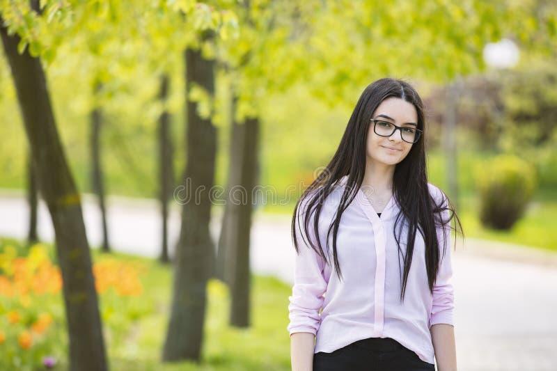 Jugendlichmädchen mit den Gläsern, die Kamera und das Lächeln betrachten lizenzfreies stockbild