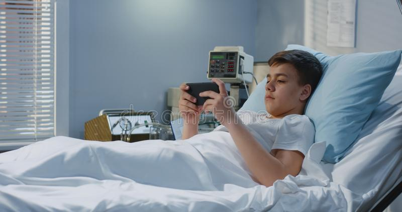 Jugendlichpatient, der mit gameboy im Krankenhaus spielt stockfotografie