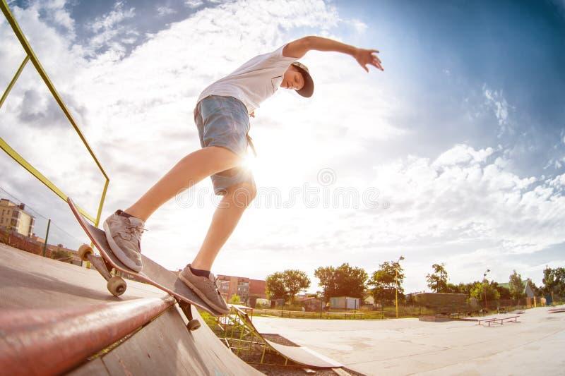Jugendlichschlittschuhläufer in einer Kappe und kurze Hosen auf Schienen auf einem Skateboard in einem Rochen parken stockfoto