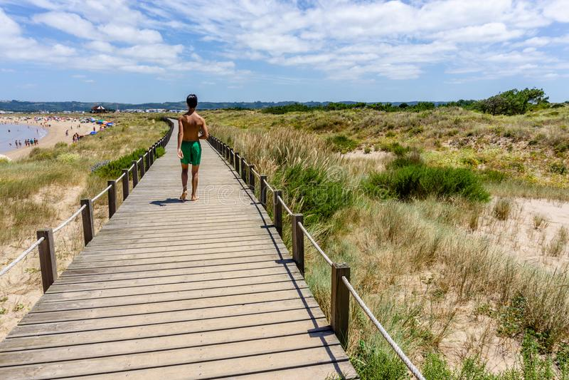 Jugendlichspaziergänge auf den Brücken auf dem Strand im Sao Martinho tun stockbild