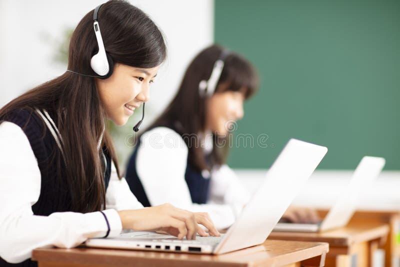 Jugendlichstudent, der online mit Kopfhörern und Laptop lernt stockbild