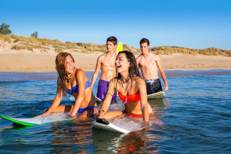 Jugendlichsurferjungen und -mädchen, die ove Surfbrett schwimmen stockfoto