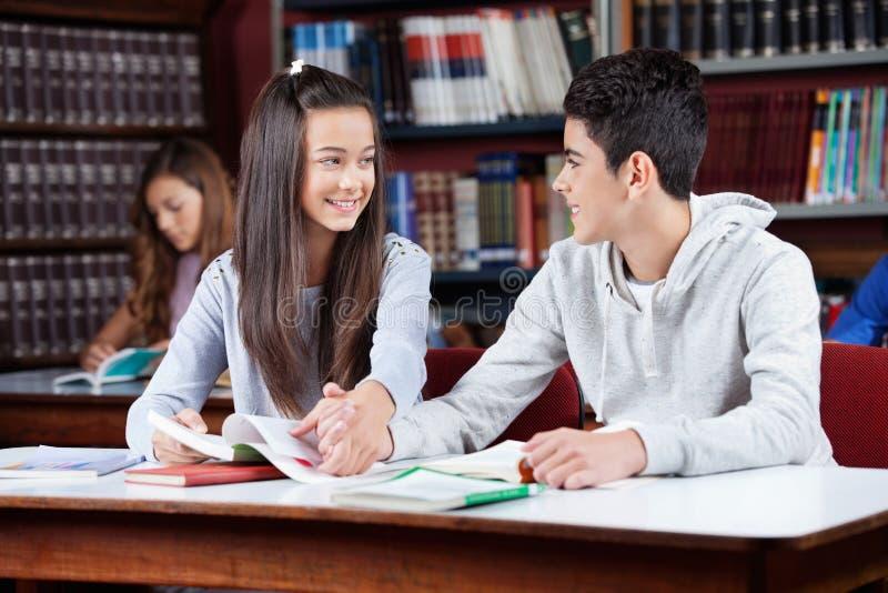 Jugendpaar-Händchenhalten bei Tisch in der Bibliothek stockbild